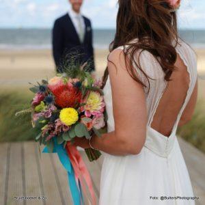 Bruidsboeket veldboeket met loshangende linten en vrolijke kleuren